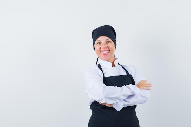 Mulher loira em pé de braços cruzados, sorrindo em uniforme preto de cozinheira e bonita.