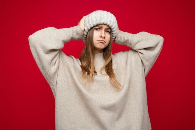Mulher loira em pé isolado sobre a parede de fundo vermelho, vestindo um suéter bege e um chapéu bege, olhando para a câmera.