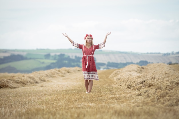 Mulher loira em pé no campo com os braços abertos