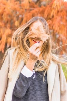 Mulher loira em pé no vento com folhas de outono
