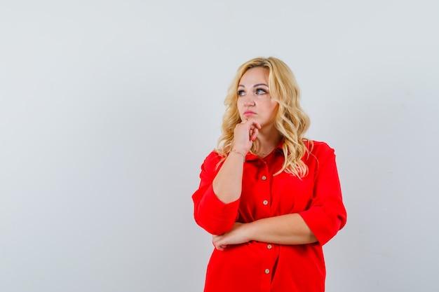 Mulher loira em pé pensando em pose de blusa vermelha e olhando pensativa.