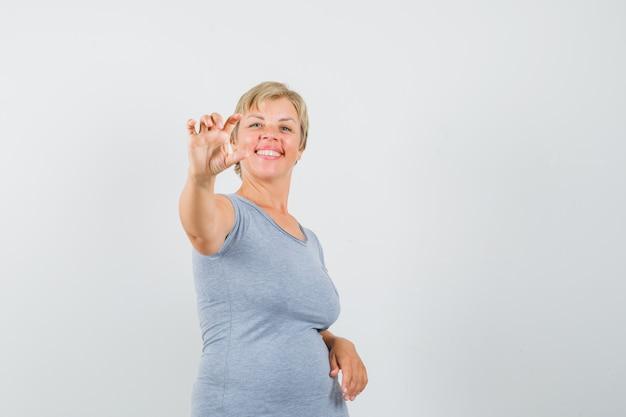 Mulher loira em pé segurando algo e sorrindo em t-shirt azul claro e olhando feliz, vista frontal.