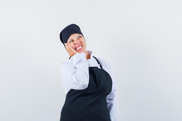 Mulher loira em pose de pensamento, inclinando a bochecha por lado em uniforme preto de cozinheiro e olhando pensativa.