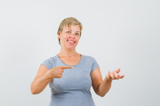 Mulher loira em t-shirt azul claro fingindo ter algo à mão apontando para ele com a outra mão e olhando alegre, vista frontal.