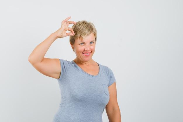 Mulher loira em t-shirt azul claro, mostrando sinal de ok e sorrindo e parecendo feliz, vista frontal.
