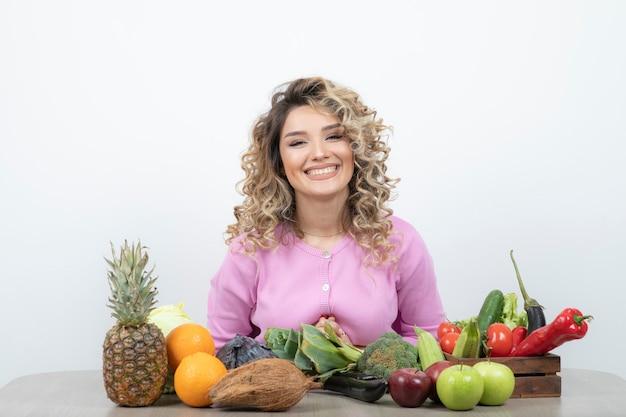 Mulher loira em top rosa sentado à mesa com muitas frutas e legumes.