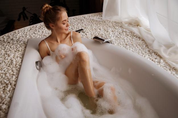 Mulher loira em um banho com espuma.