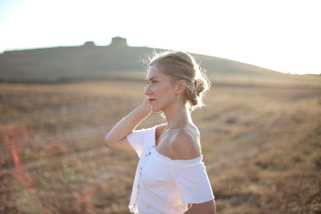 Mulher loira em um campo seco sob o sol