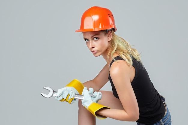 Mulher loira. em um capacete de proteção e luvas, segurando uma grande chave inglesa.