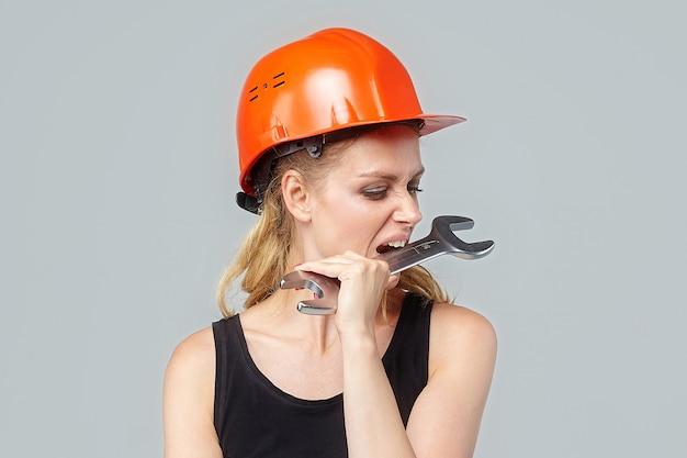 Mulher loira. em um capacete protetor tem uma grande chave inglesa nas mãos.