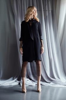 Mulher loira em um casaco de outono preto fica