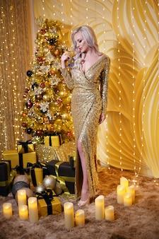 Mulher loira em um conjunto de natal dourado