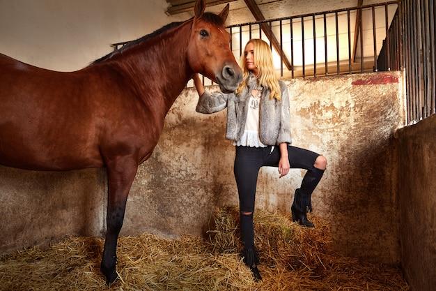 Mulher loira em um estábulo interior com cavalo