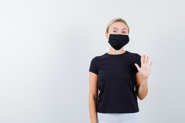 Mulher loira em uma camiseta preta, calça branca, máscara preta mostrando uma placa de pare