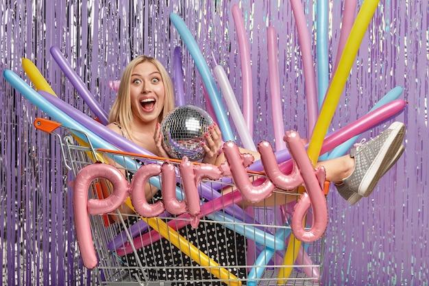 Mulher loira em uma festa no carrinho de compras segurando balões
