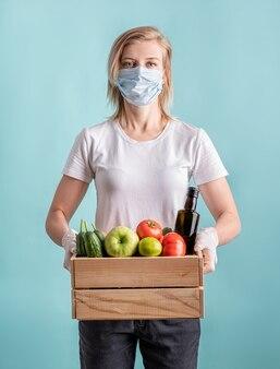 Mulher loira em uma máscara e luvas segurando uma caixa de madeira