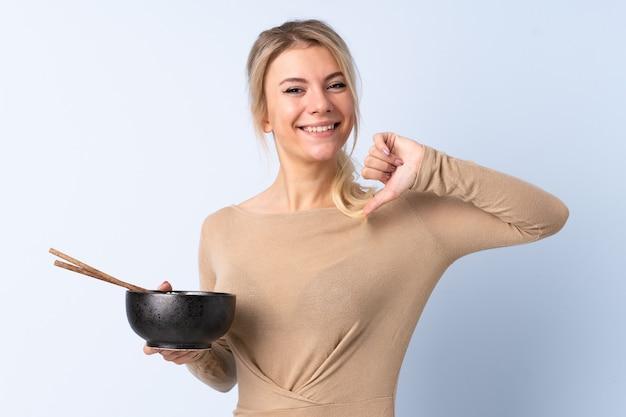 Mulher loira em uma parede azul isolada, orgulhosa e satisfeita, segurando uma tigela de macarrão com pauzinhos