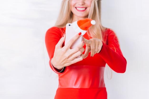 Mulher loira em vermelho tomando selfie com telefone