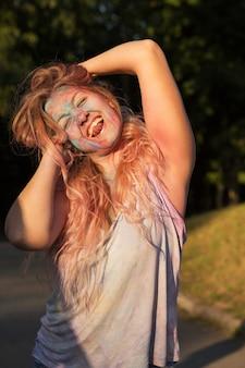 Mulher loira emocional com longos cabelos cacheados coberto com tinta seca colorida, comemorando o festival holi