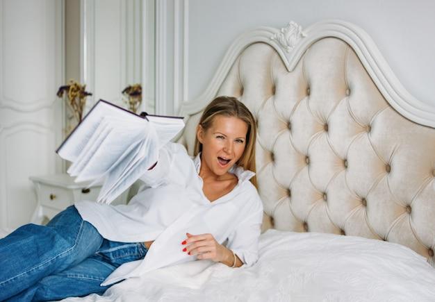 Mulher loira encantadora amigável com cabelo longo loiro em roupas casuais com livro na cama no interior rico brilhante