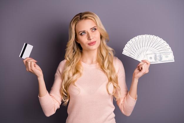 Mulher loira encantadora com suéter rosa posando com dinheiro contra a parede roxa