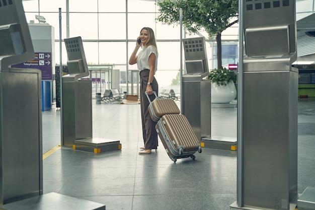 Mulher loira encantadora com um sorriso no rosto enquanto fica em pé na semi-posição carregando sua bagagem