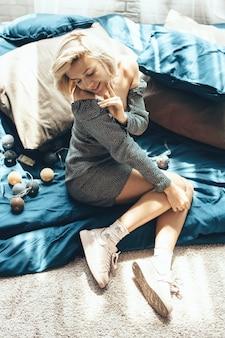 Mulher loira encantadora com um vestido e deitada no chão perto de uma colcha com almofadas e luzes de ano novo
