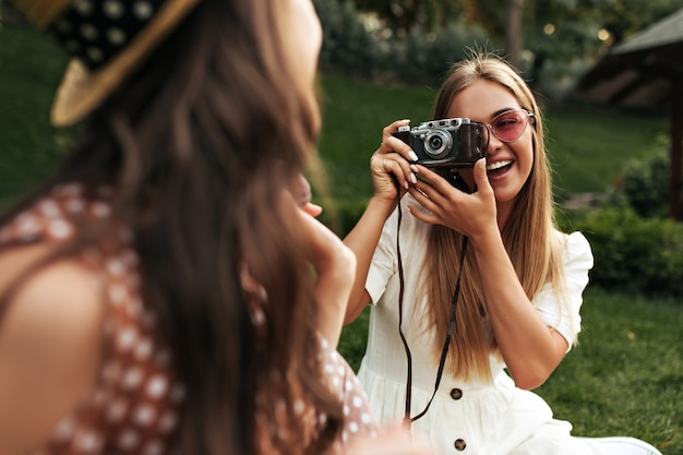 Mulher loira encantadora com vestido branco estiloso e óculos de sol vermelhos, sorri e tira uma foto da amiga