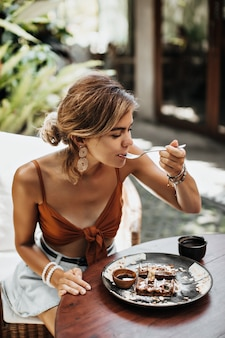 Mulher loira encantadora de sutiã marrom e shorts jeans come waffle com calda de creme e chocolate e aprecia seu sabor
