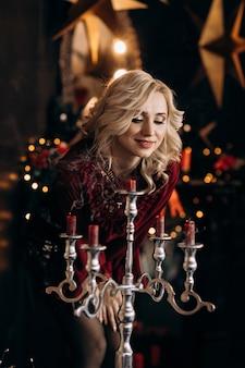 Mulher loira encantadora olha velas em pé na sala com uma bela decoração de natal