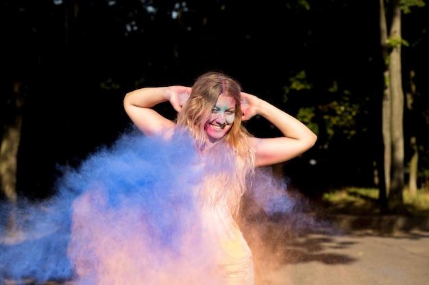Mulher loira encantadora se divertindo com tinta holi seca explodindo
