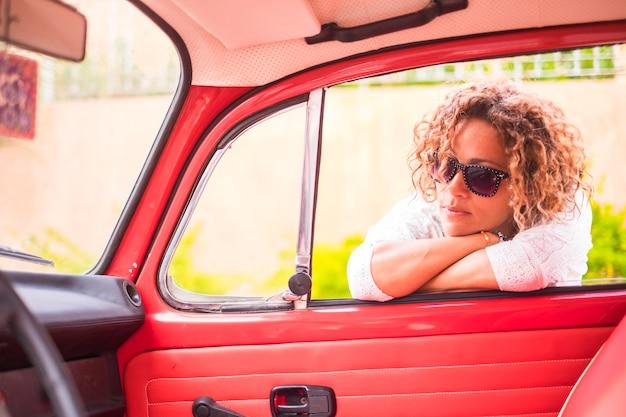 Mulher loira encaracolada de meia-idade, pensativa e bonita, sorrir e desfrutar da atividade de lazer ao ar livre perto de seu carro clássico vintage vermelho. pronto para viajar e viver o dia