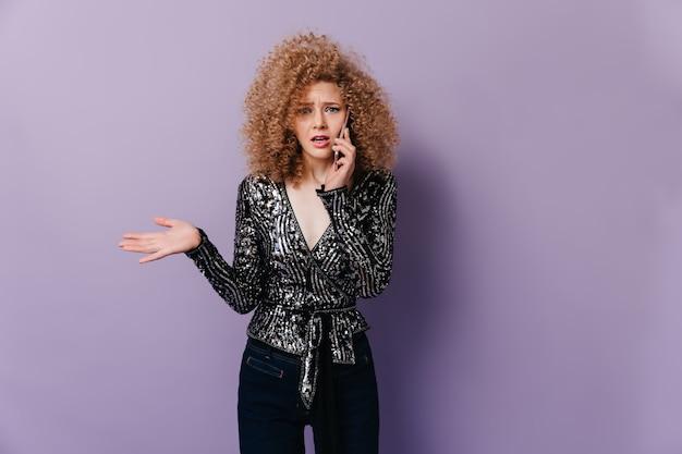 Mulher loira encaracolada insatisfeita no top brilhante com mangas compridas, falando no telefone no espaço lilás.