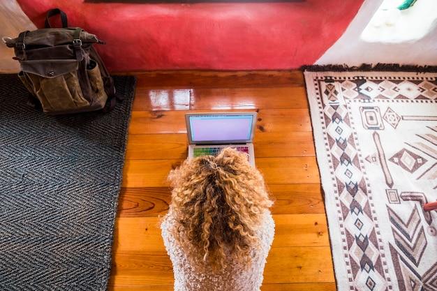 Mulher loira encaracolada trabalhando no laptop deitada no chão de um hotel ou quarto de casa, vista de cima