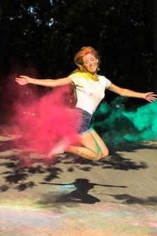 Mulher loira engraçada pulando com cores vibrantes explodindo ao seu redor