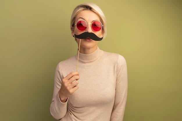 Mulher loira engraçada usando óculos escuros segurando um bigode falso acima dos lábios, olhando para a frente, isolada na parede verde oliva com espaço de cópia