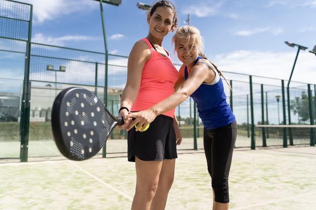 Mulher loira ensinando outra mulher a segurar uma raquete de padel enquanto sorria em uma quadra de padel ao ar livre