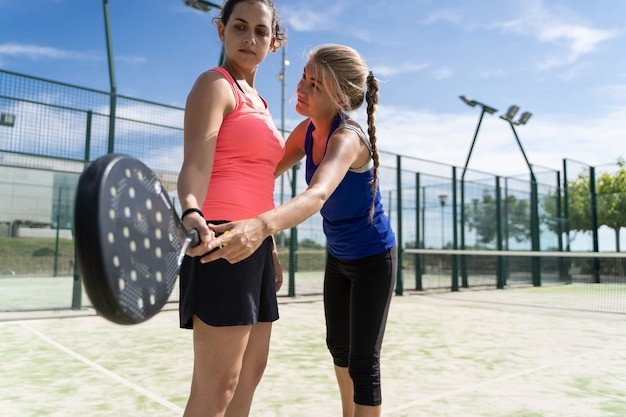 Mulher loira ensinando outra mulher a segurar uma raquete de padel