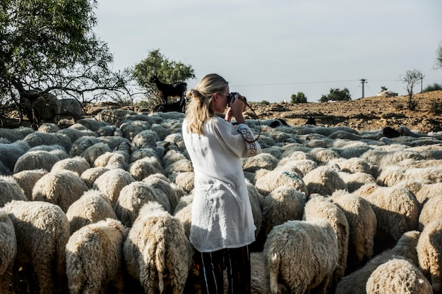 Mulher loira entre um rebanho de ovelhas