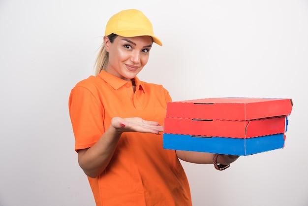 Mulher loira entregadora segurando caixas de pizza.