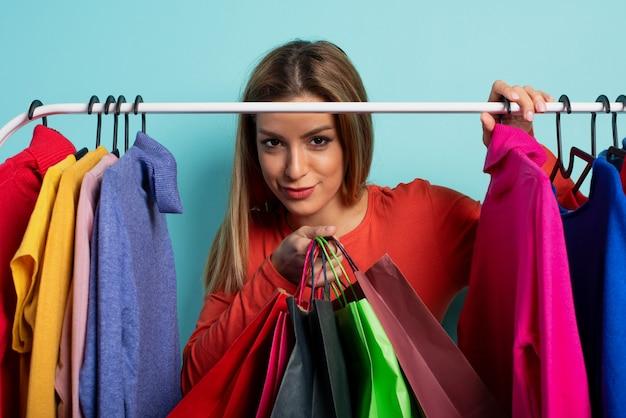 Mulher loira escolhe as roupas para comprar na loja