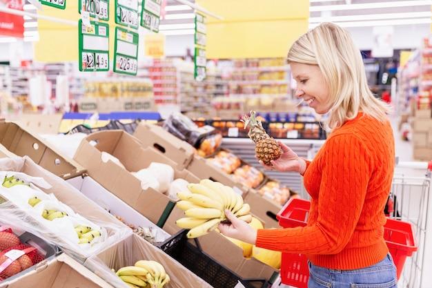 Mulher loira escolhe frutas no supermercado.