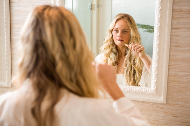 Mulher loira, escovando os dentes no banheiro em casa