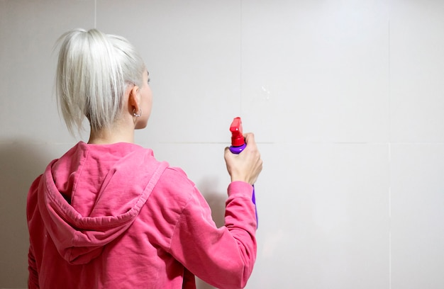 Mulher loira, escovar o cabelo com pente no banheiro