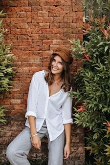 Mulher loira escura em uma blusa grande e calças de excelente humor, posando ao lado de uma velha parede de tijolos e árvores.