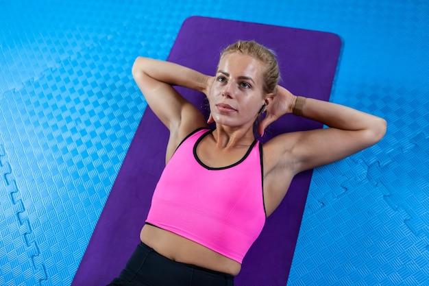Mulher loira esporte deitada na esteira e exercitando os músculos abdominais na academia, exercícios para a parte inferior do corpo. atividade esportiva para perda de peso
