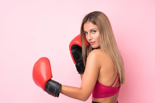 Mulher loira esporte jovem com luvas de boxe sobre rosa isolado