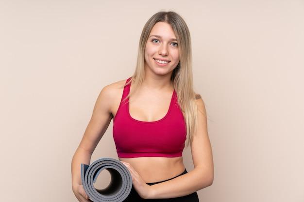 Mulher loira esporte jovem com uma esteira e sorrindo