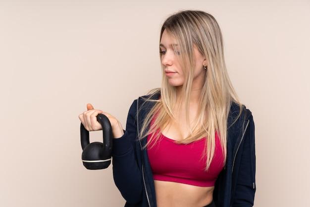 Mulher loira esporte jovem fazendo levantamento de peso com kettlebell