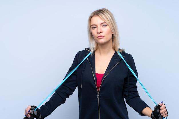 Mulher loira esporte jovem isolado parede azul com pular corda